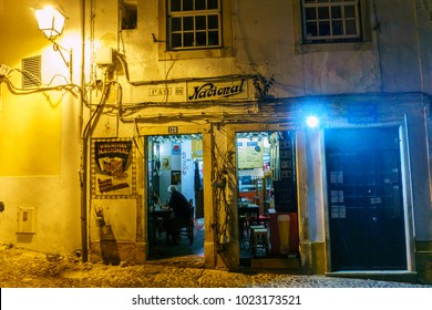 Coimbra, Portugal, August 13, 2018: Night view of a typical and famous restaurant on the ground floor and tourists having dinner