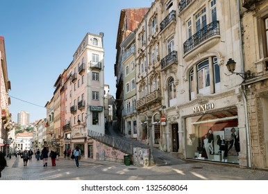 COIMBRA, PORTUGAL - MARCH 13, 2014: People walking at Narrow Street with ancient houses in Old Town, Coimbra, Portugal