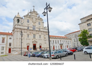 Coimbra, Portugal - Sep 4th 2018: Beautiful building of New Cathedral of Coimbra with nearby parking place and visitors walking in this Roman Catholic monument taken during a cloudy summer day.