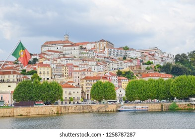 Coimbra, Portugal - Sep 4th 2018: Beautiful old town of Coimbra from the Santa Clara Bridge with portuguese flag on the left. The most remarkable sight is the local university on the top of the hill.