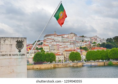 Coimbra, Portugal - Sep 4th 2018: Beautiful view of the historical center of Coimbra with portuguese flag blowing in the wind. Taken from the Santa Clara Bridge over the Mondego River.