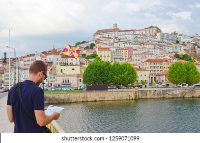 Coimbra, Portugal - Sep 4th 2018: Caucasian tourist man in dark blue t-shirt reading the map on the Santa Clara Bridge over the Mondego River. The beautiful historical old town is in the background.