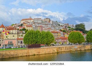 Coimbra, Portugal - Sep 4th 2018: Awesome scenery with historical old town of portuguese Coimbra taken from the Santa Clara Bridge over the Mondego River on a cloudy summer day.