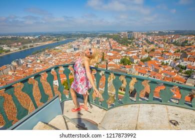 Coimbra Santa Clara Bridge on Mondego river. Caucasian tourist woman admiring Coimbra panorama sitting on top of bell Clock Tower.