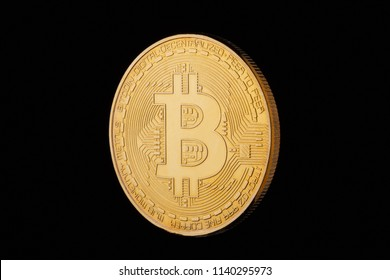Coin bitcoin made of gold, isolated on a black background.