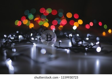 Coin of bitcoin payment system with decentralisation and electronic wallet. Festive atmosphere. Cold white Christmas tree lights in the background. BTC is a cryptocurrency.