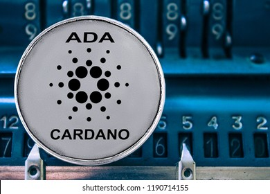 Coin of Cardano on the background of numbers adding machine. The concept of production or rate of ada.