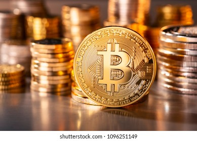 Coin of the crypto-currency Bitcoin with several stacks of coins in the background
