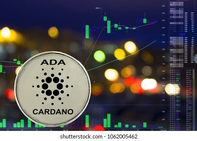 Coin cryptocurrency Cardano on night city background and chart.