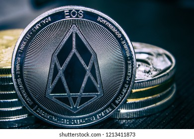 The Coin cryptocurrency EOS on the background of a stack of coins.