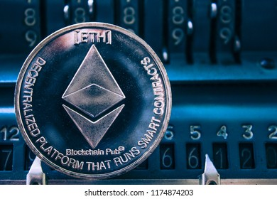 Coin cryptocurrency Ethereum on the background of numbers adding machine. The concept of production or rate of ETH.