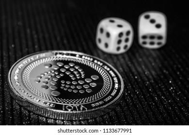 Coin cryptocurrency iota and rolling dice. Miota