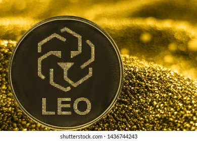 Coin cryptocurrency Leo and gold fabric background. bifinex token logo.