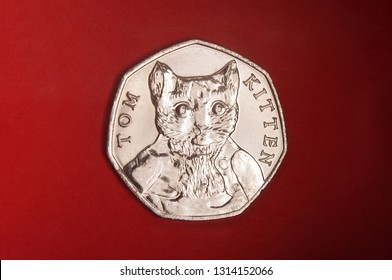 Coin dedicated to Beatrix Potter The tale of Peter rabit 50 pence isolated on the red background
