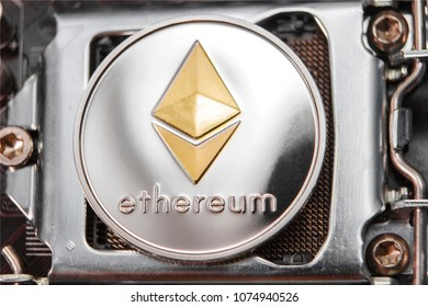 Coin ethereum on the background of a microcircuit. Crypto currency etherium close-up. Mining. Crypto. Close up photo of Gold ethereum coins on computer main board, concept of cryptocurrency mining
