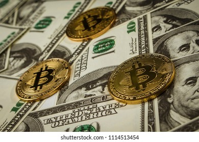 Coin in the form of bitcoin on a pile of dollar bills