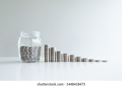 coin in glass bottle bank with coins bar graph, step up growing business to success and saving for retirement concept.