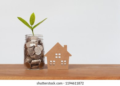 Coin in glass bottle or plant growing on coins in glass jar with house model with white background. Money for business planning investment. Investment and saving concept