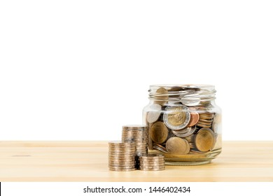 Coin glass jar container and stack on wooden desk, saving concept, on white background