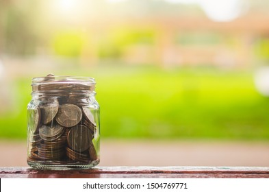 coin in to glass jar saving money concept. business and financial budgeting for investment startup business.