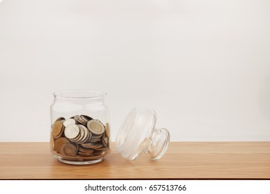 Coin in glass on wooden table for investment and interest concept