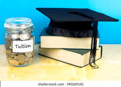 Coin in the jar with text tuition, books and graduation hat on wooden background.