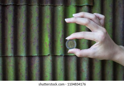 coin money hand background zinc green old date 4/6/2061