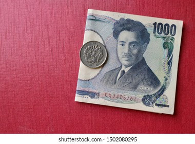 Coin on Japanese money on red paper background
