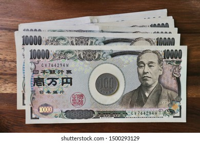Coin on pile of Japanese money on wood table