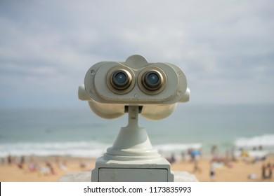 Coin operated binocular on the summer beach, tourist scene in Spain