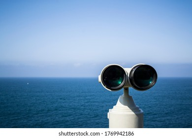 Coin operated binocular viewer along the promenade overlooking the bay and the city. Beautiful landscape of sky and sea.