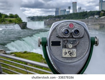 A coin operated binocular viewer located in Niagara Falls with a view to the falls out of focus in the background.