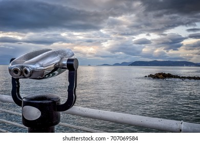 Coin Operated Binocular viewer next to the waterside pier in Massa looking out to the Bay and city. Landscape with beautiful cloudy sky, sea and mountains .View over Portovenere and five lands