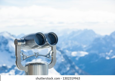 Coin operated Binoculars with snowy Mountains in the Background - Concept for Business Outlook or future Perspective