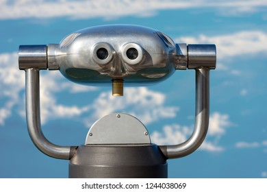 Coin operated electronic binoculars for tourists on a blurred blue sky with clouds