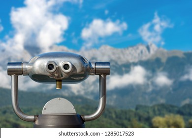 Coin operated electronic binoculars for tourists on a blurred mountain landscape