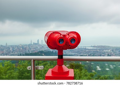 Coin operated red binocular towerview on observation deck with view on the sea and city