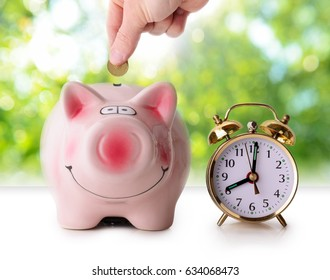 Coin in piggy bank with retro alarm clock