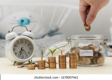 Coin sapling and alarm clock in the piggy bank