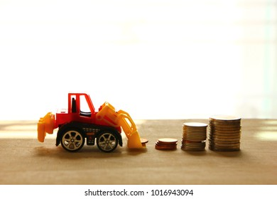 coin stack  with construction toy on  wooden floor
