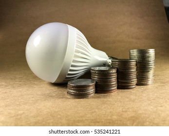 Coin Stack And Led bulb, Brown background