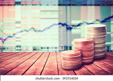 coin stack on old wooden floor with blur image of graph stock market background