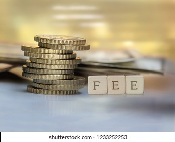 Coin stack and wooden blocks with the fee text. Fee Finance and Money concept.