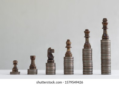 Coin stacks arranged with chess pieces into growth chart on white background, finance and business concept, copy space
