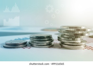 Coin stacks on paper of financial graph. Graphics icons, worldwide stock exchanges. Business concept. Color filter.