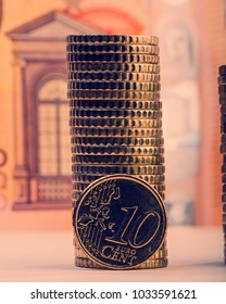 coin of ten euro cents on the background of folded coins and a paper bill of fifty euros. Euro money.  Currency of the European Union.