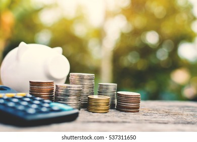 coin  with white piggy bank calculator on old wood and tree bokeh background with sunlight , a color of vintage tone concept save money