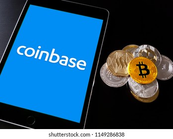 Coinbase cryptocurrency exchange logo on ipad smart device with stack of cryptocurrencies. Copenhagen / Denmark - 08 05 2018