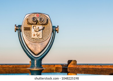 Coin-operated binoculars in early morning light, on a fishing pier with a view of ocean waves in the distance.