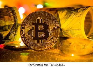 Coins bitcoin and dollars are twisted, in the light of the colorful side